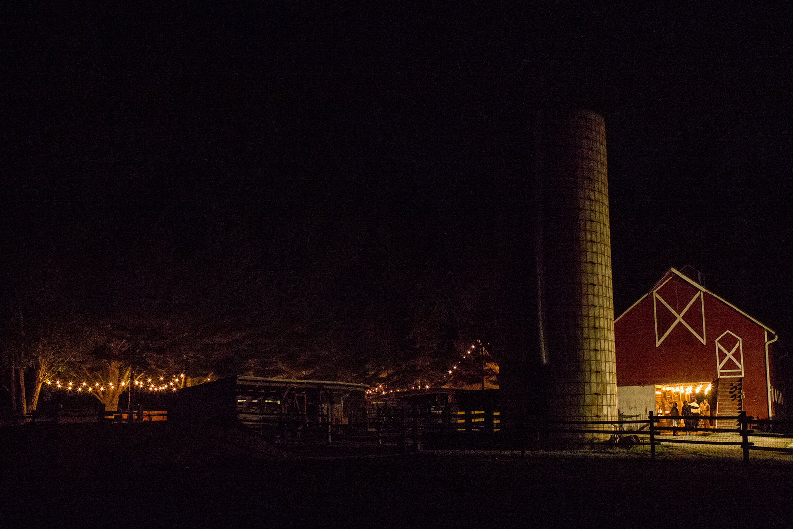 shot of milston well farm at night, showing a red barn where bistro lights hang inside and a file and fences out front