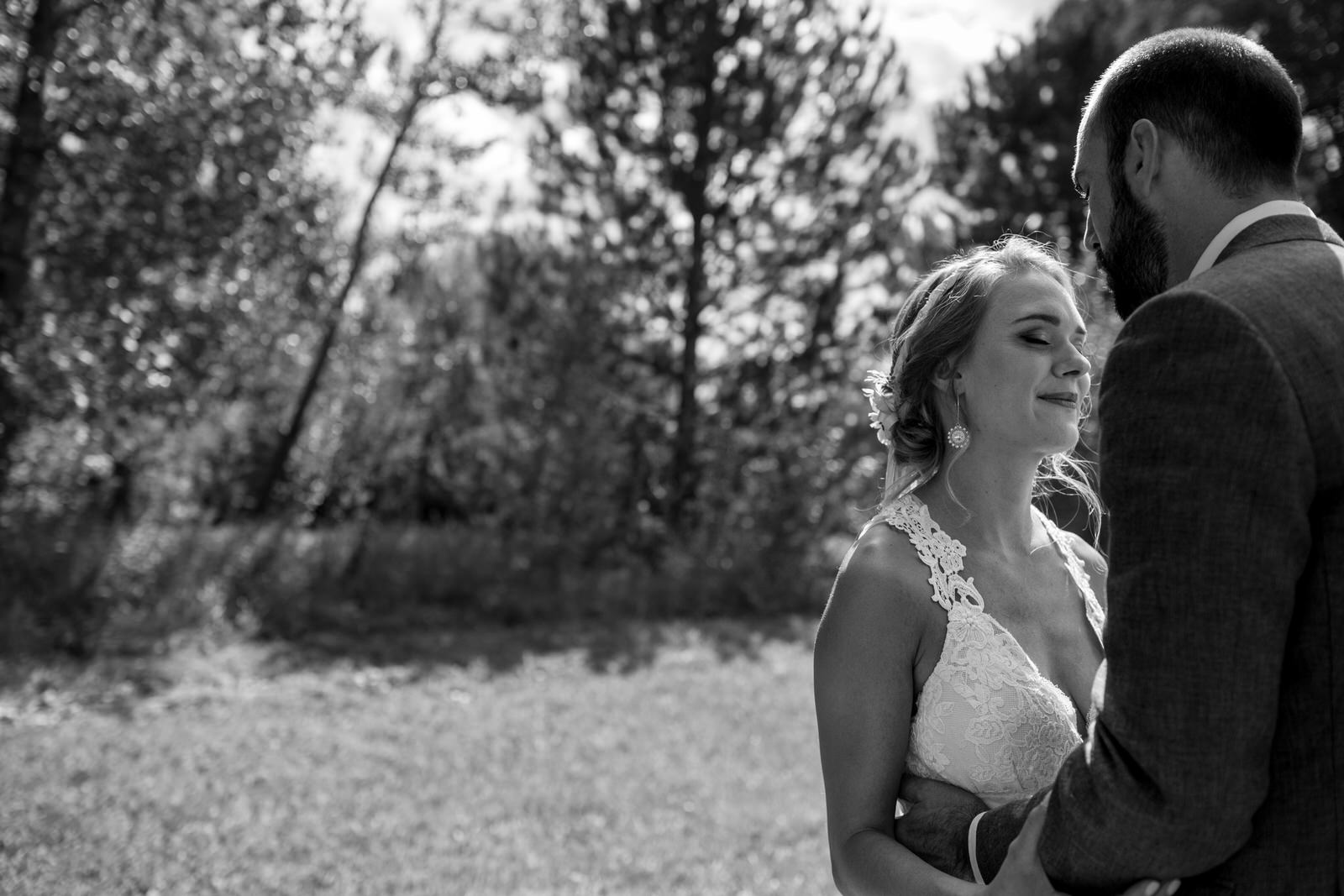 black and white of a groom embracing his bride as he is about to kiss her in a field at their lone hawk farm wedding wedding
