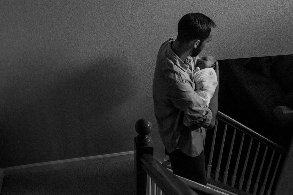 dad carrying newborn baby down the stairs during a boulder newborn photography session