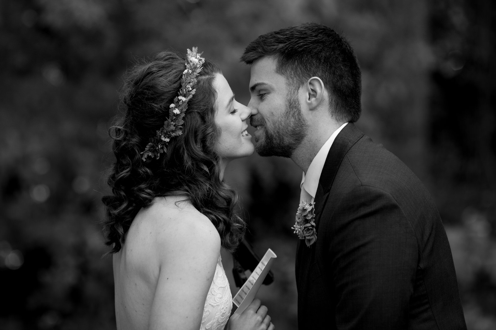 black and white close up of a bride and groom as they about to kiss each other while reading each other their vows