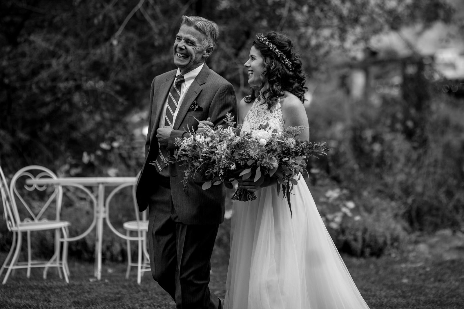 in black and white bride and her father laughing as they walk down the aisle at an outdoor wedding