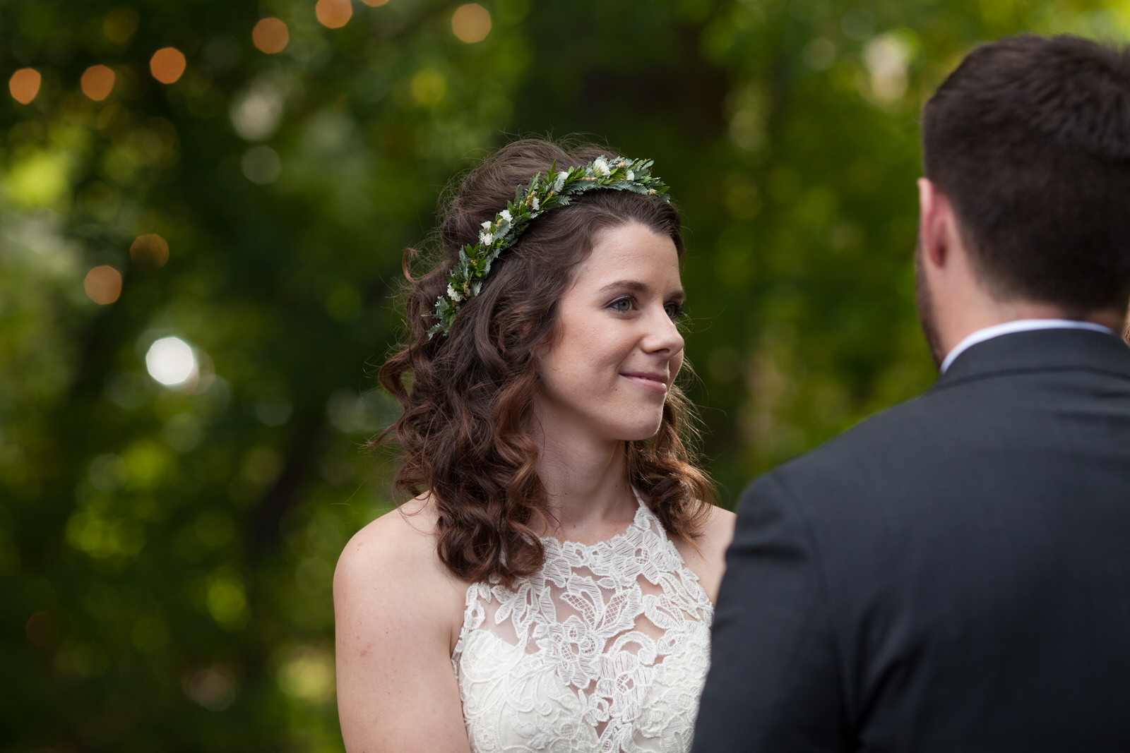a bride at an outdoor wedding with a flower crown on looking smittenly at the groom