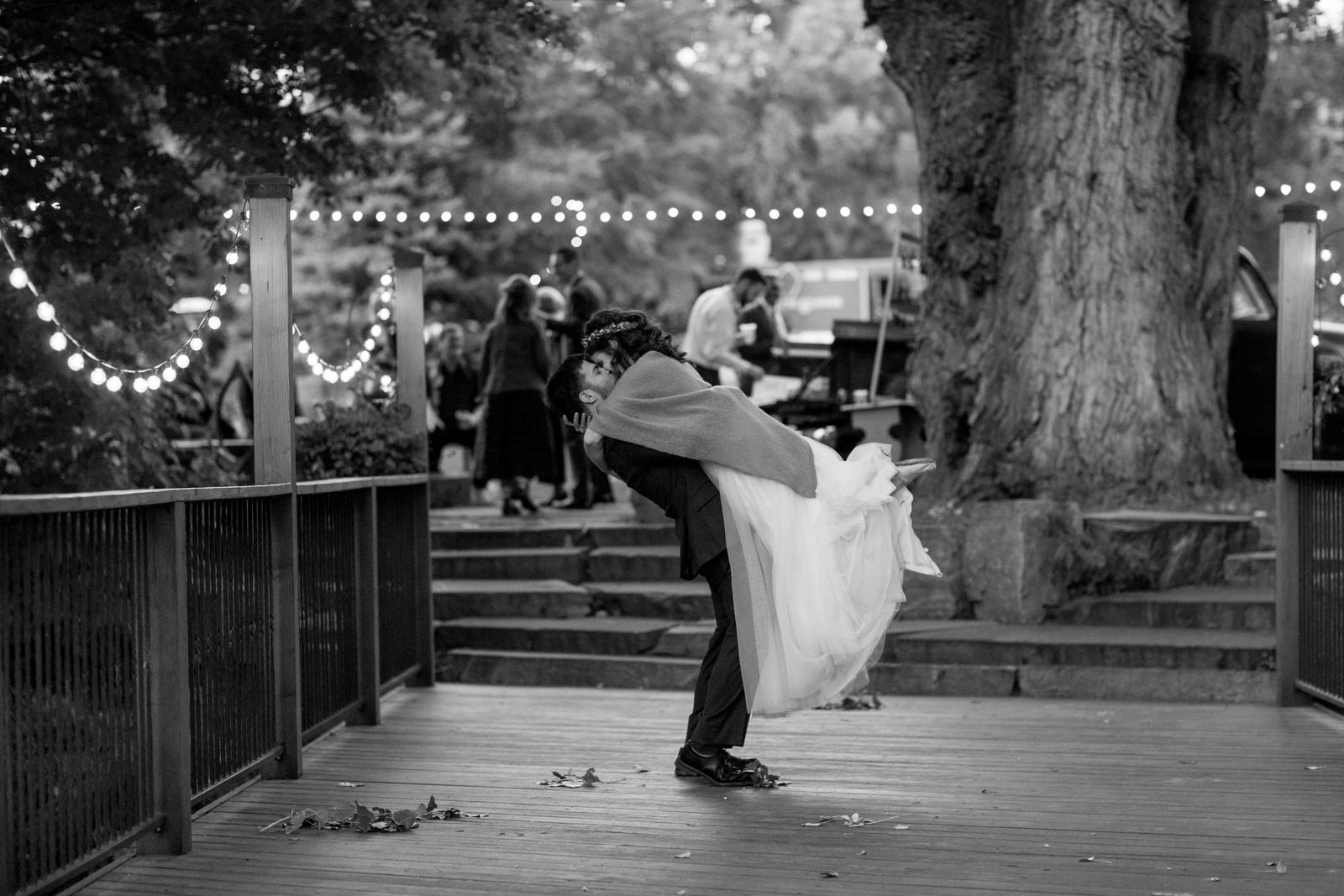 black and white photo of a groom lifting up his bride and kissing her as she kisses him back tightly in the air