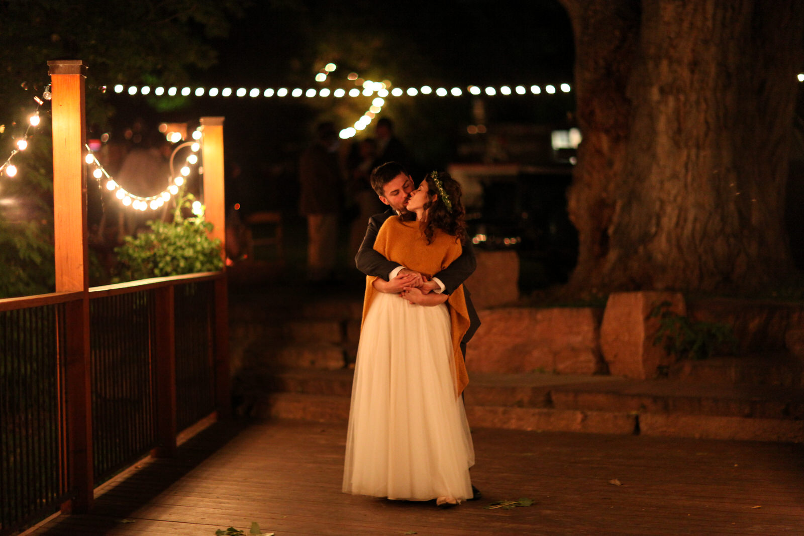 groom kissing a bride from over her shoulder under bistro lights at the end of an outdoor wedding