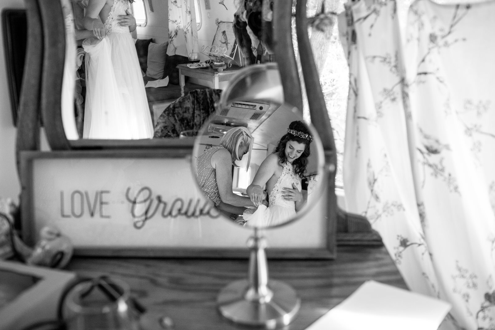 black and white photo in a mirror of a mom helping a bride button her dress
