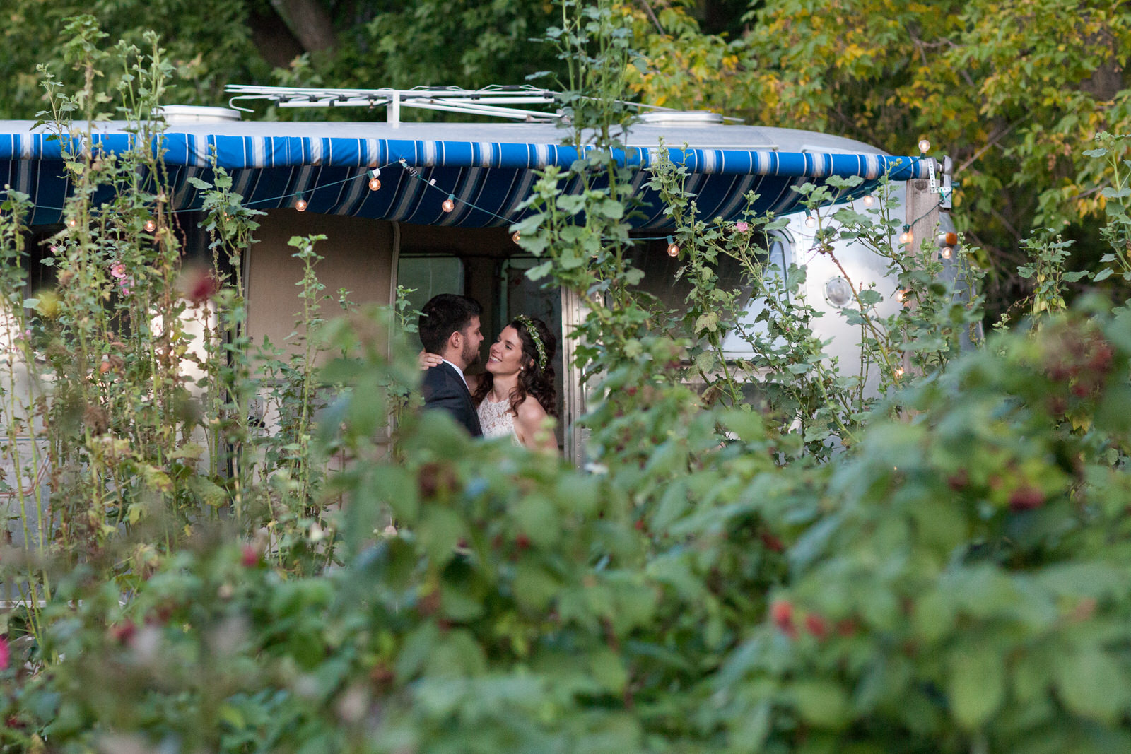 bride and groom in the door of an airstream looking lovingly at each other surrounded by greenery