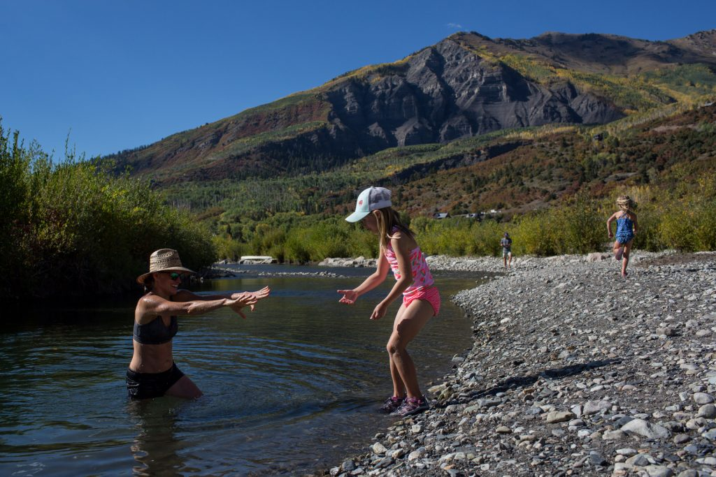 little girl helping mom get out of river during marble vacation session summer