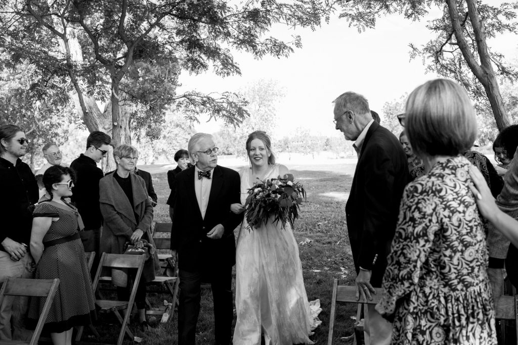 father walks bride down aisle at outdoor wedding milston well farm in colorado