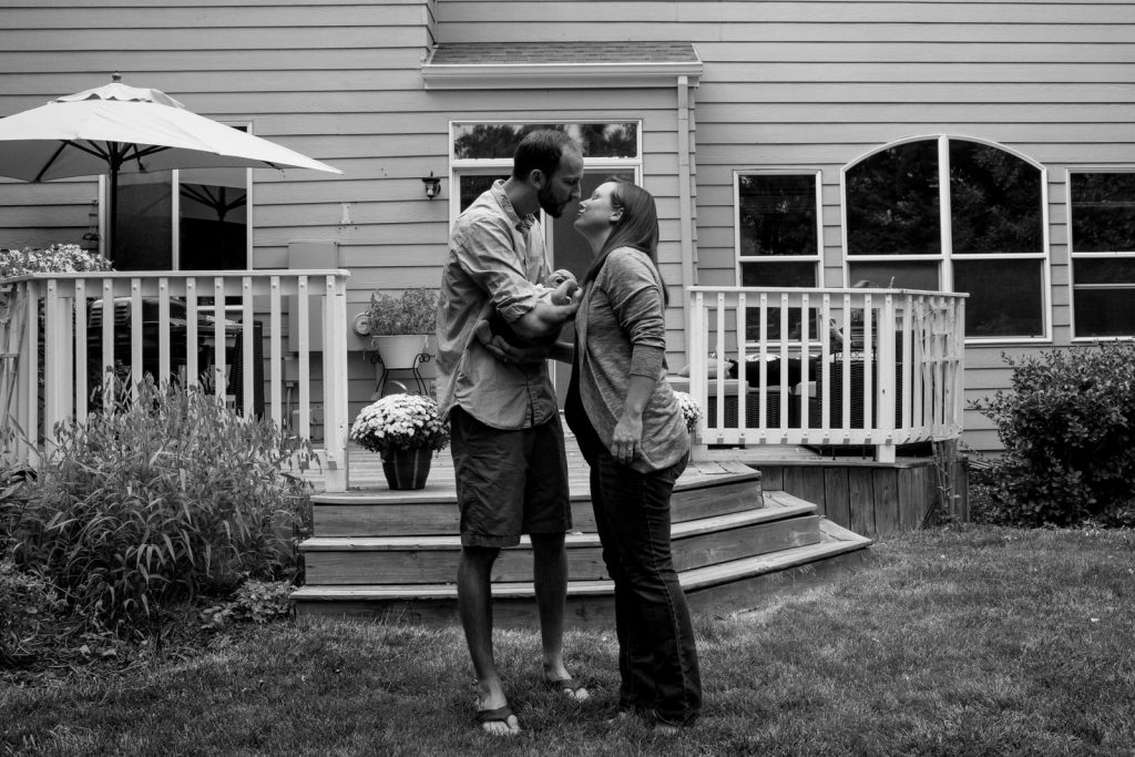 mom and dad kissing outside their home