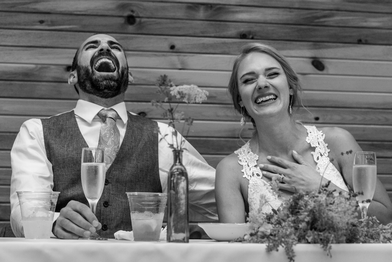black and white of a wedding couple laughing hysterically during the wedding toasts at lone hawk farm