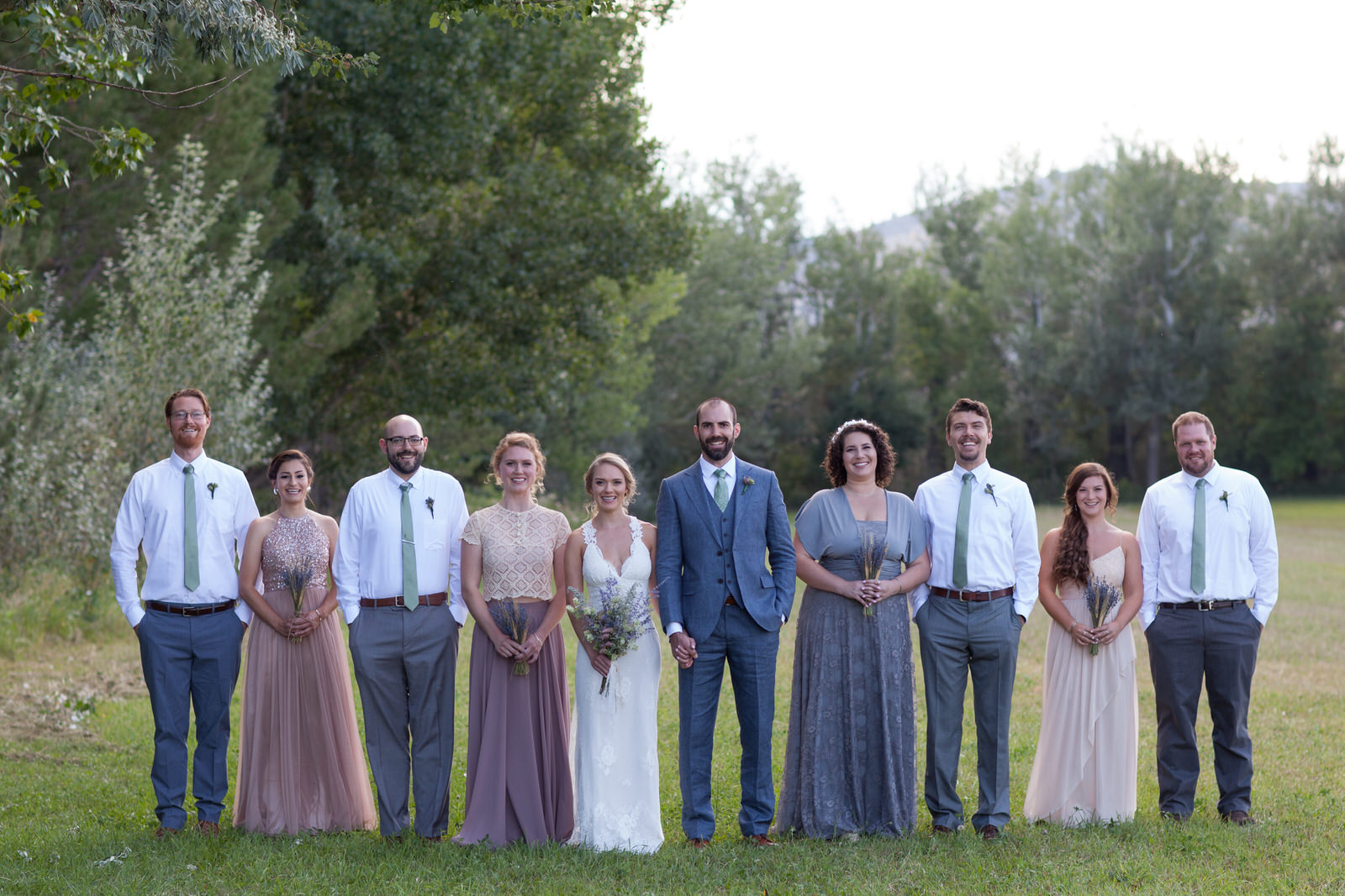 wedding party dressed in neutrals lined up in one row in a field at lone hawk farm wedding