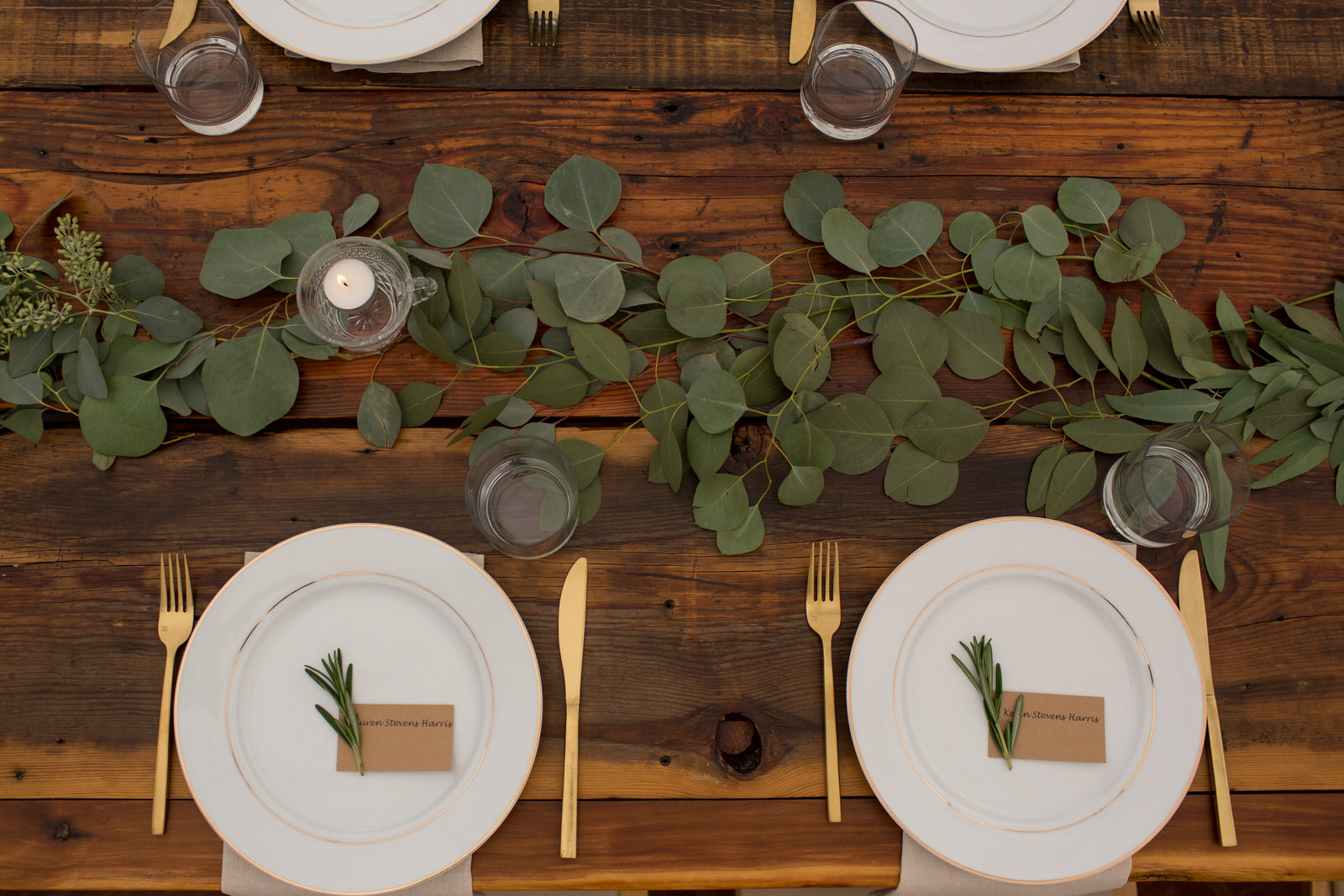 table scape from above, of a wedding table with greenery, gold rimmed plates and gold silverware
