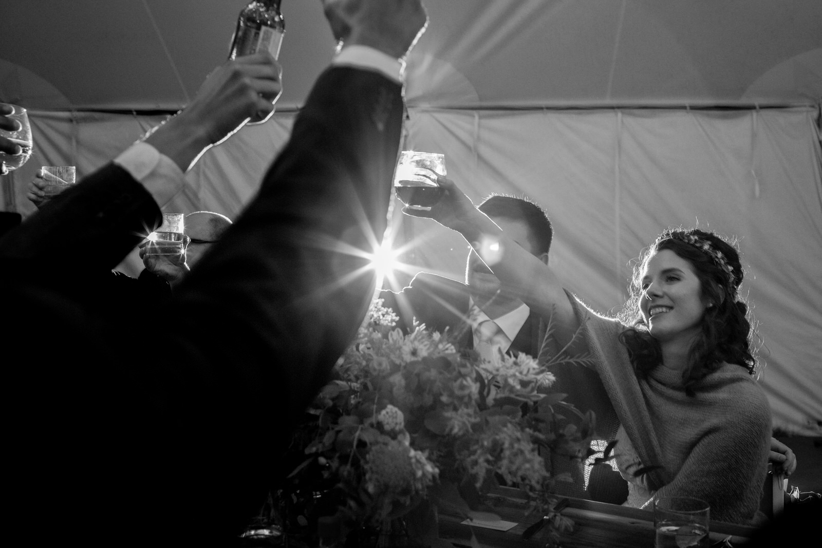 a black and white photo of a bride smiling and toasting with guests at the table