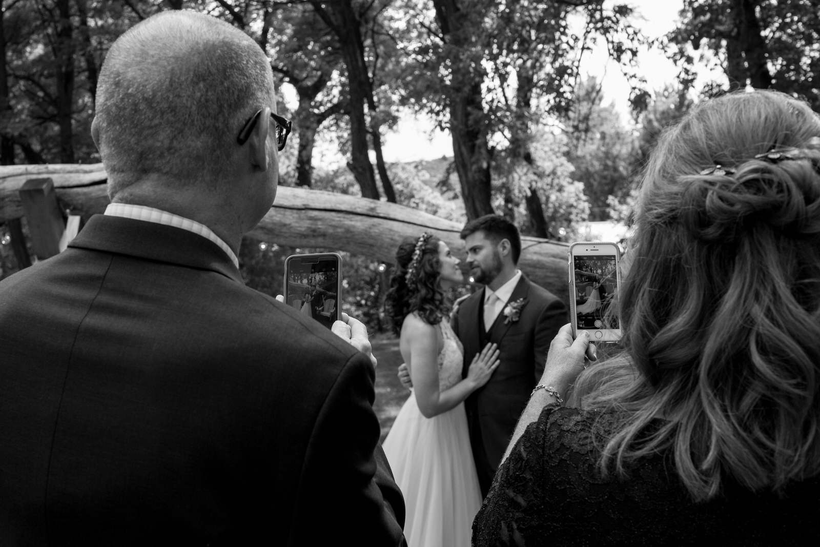 black and white of parents of the groom taking photos of the couple with their smartphones