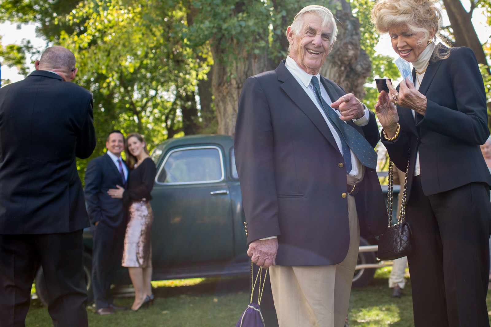 at an outdoor wedding an elderly couple in the foreground, the man laughing and pointing at the camera, in the background a couple posing for a photo against an old pick up