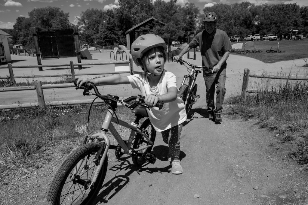 kid with tongue sticking out and pushing her bike at the Valmont bike park