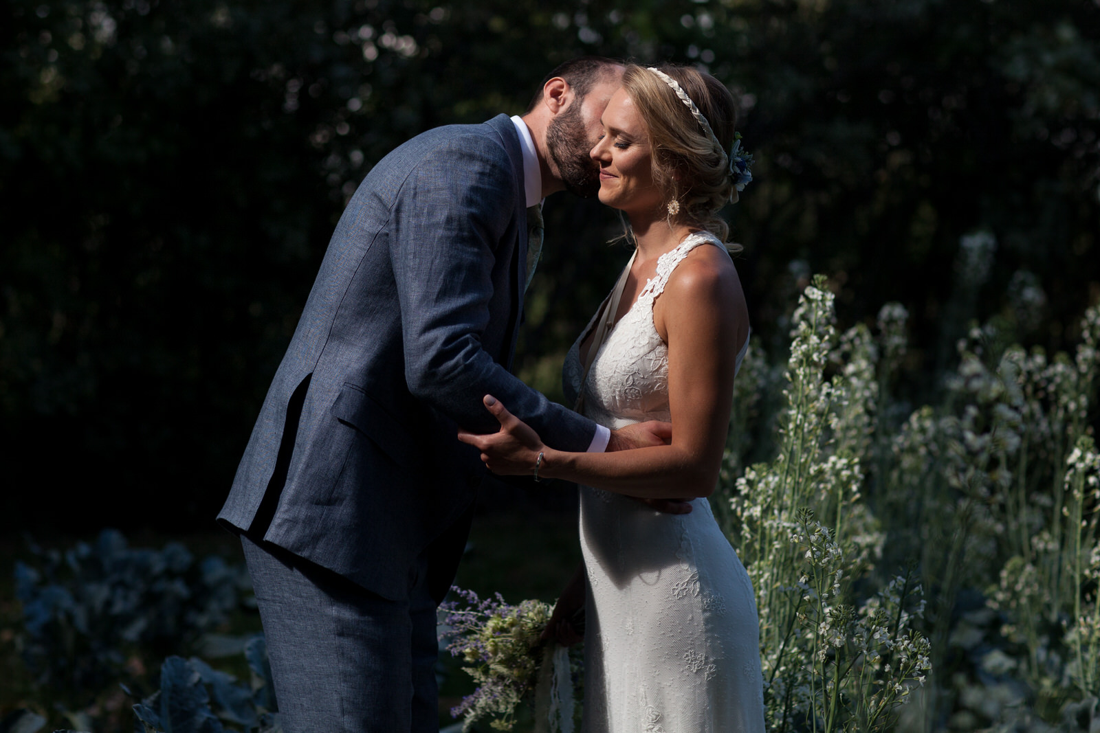 a groom kissing his bride on the cheek in bright sunlight in a garden at the farm wedding