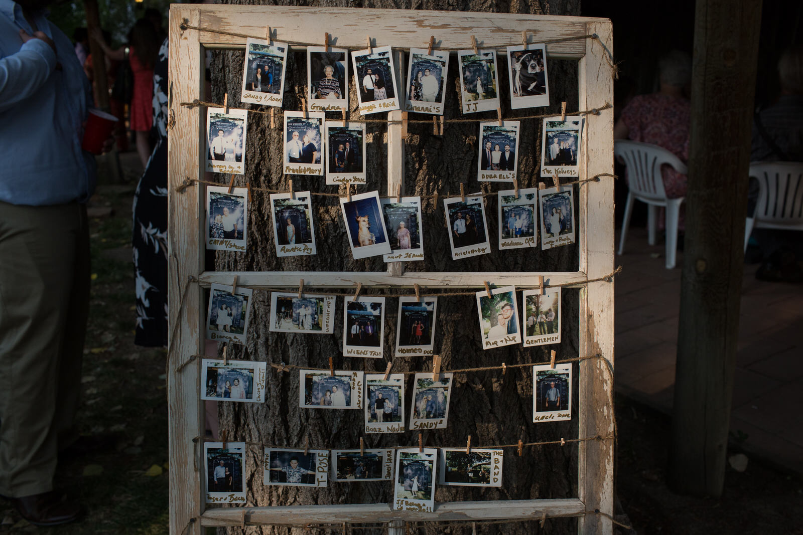 weathered window frame with chipped white pant and twine strung across it where polaroids hang with clips