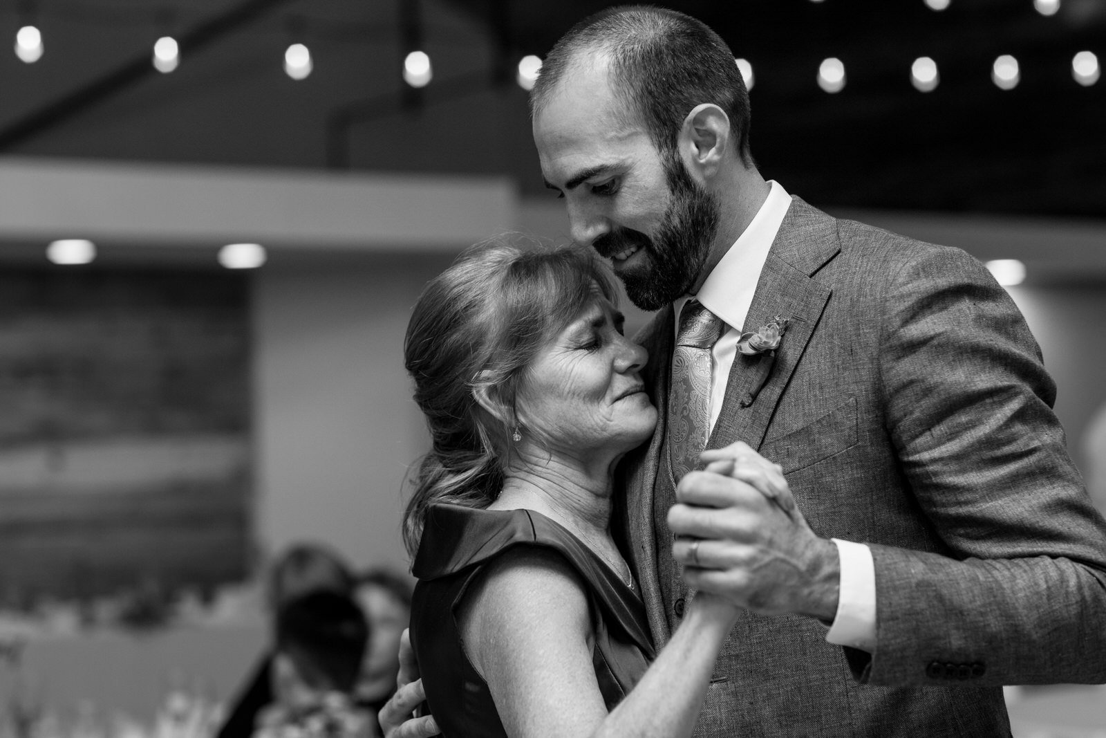 black and white of the mother son dance at a wedding as the mother is about to cry