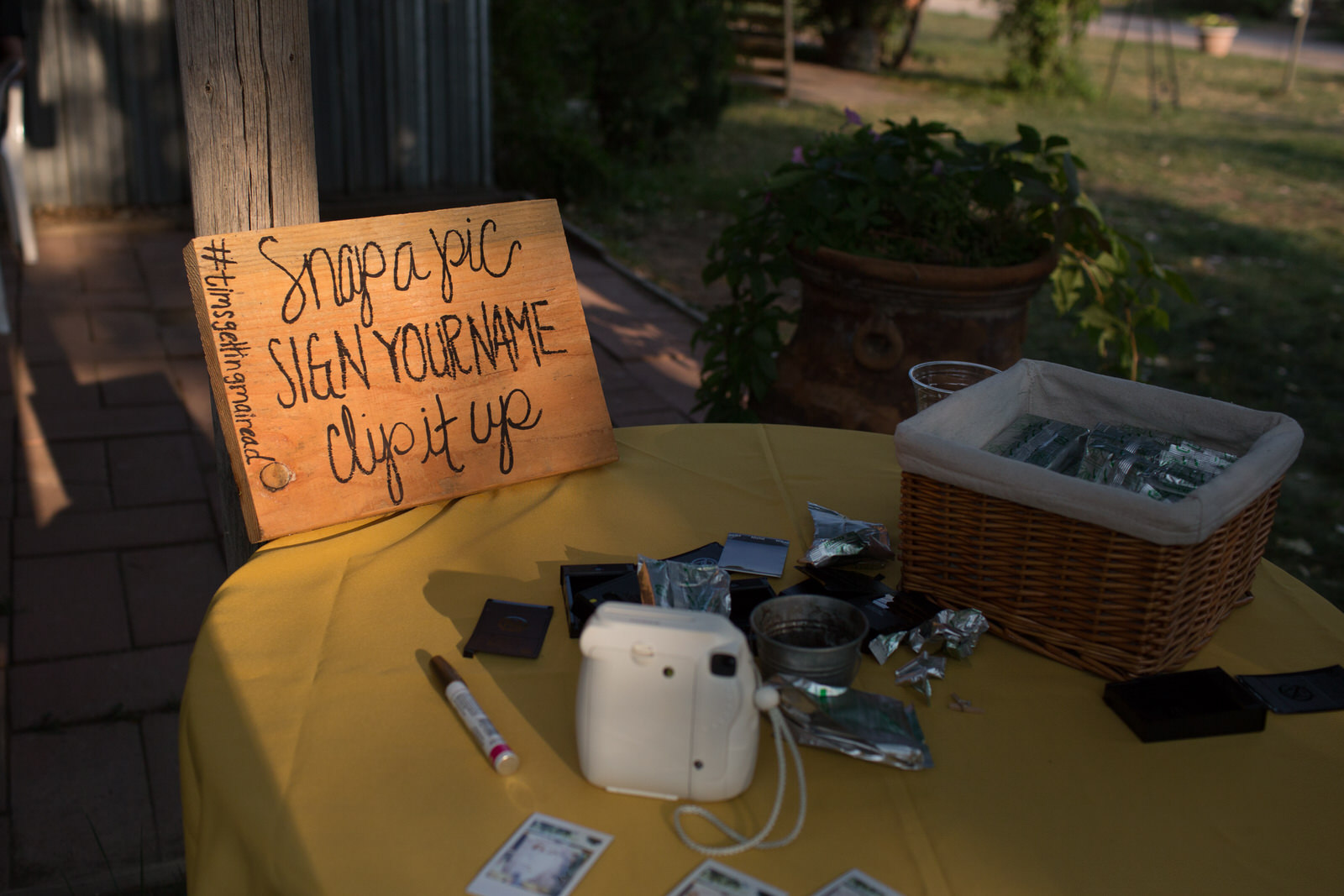 polaroid camera, film and a snap a pic wooden sign at an outdoor wedding