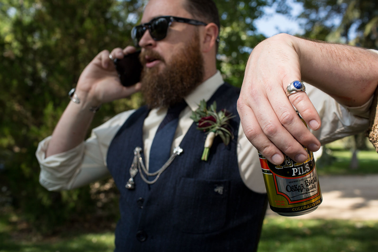 close up of groom's blue stone pinky ring sparkling in the sunlight as he holds a beer can and talks on the phone