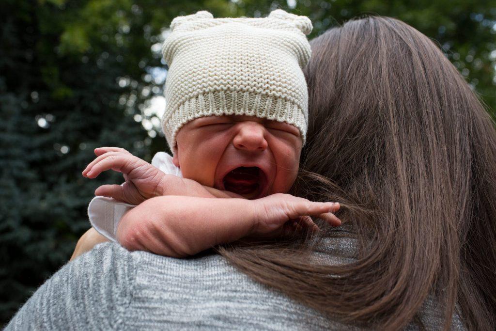 newborn baby in winter hat cries on mom's shoulder