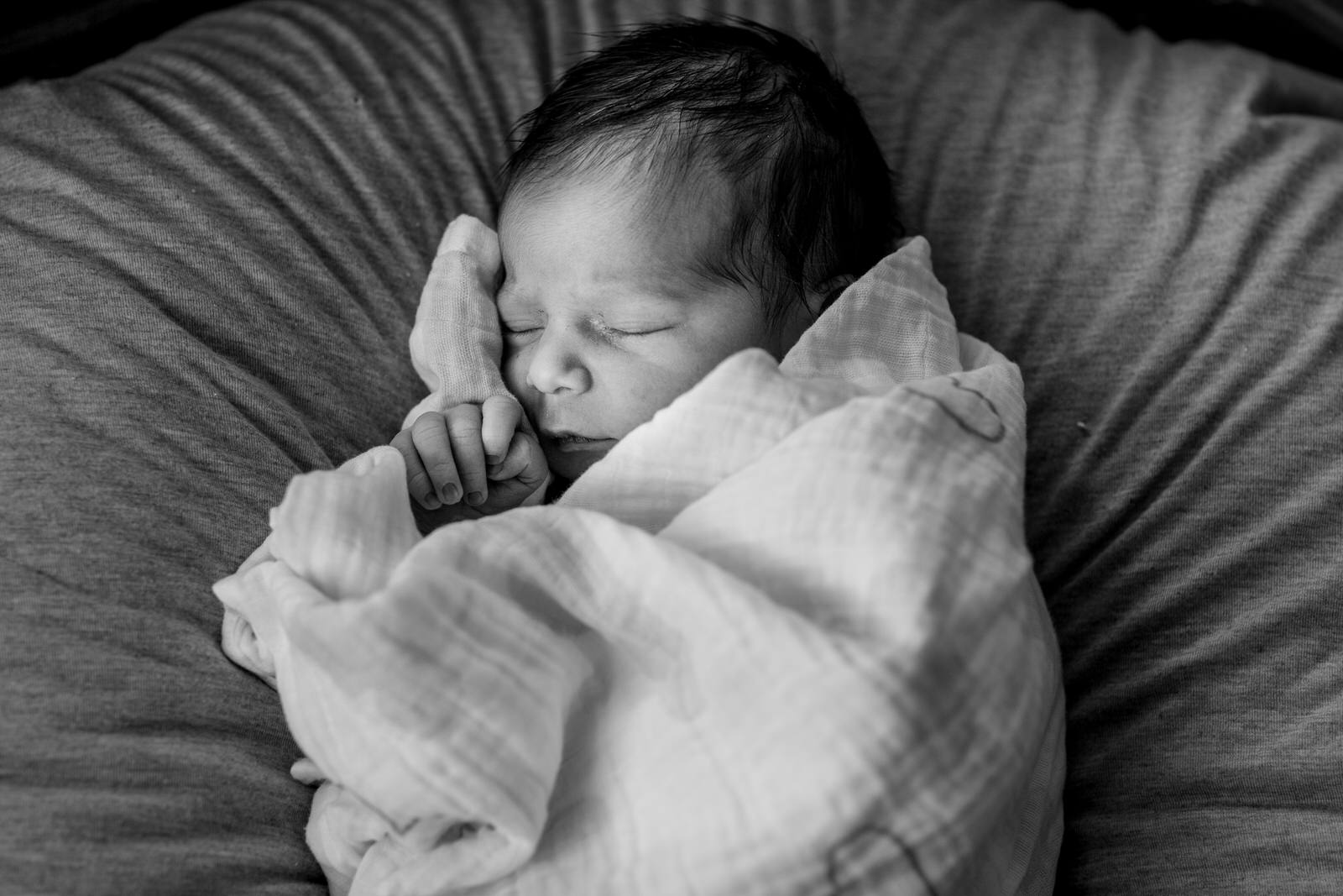 a black and white image of a newborn swaddled on a pillow trying to get her arms out