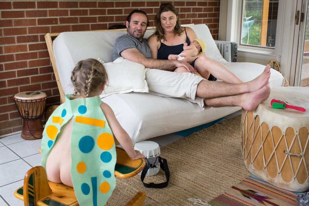 dad and mom on couch with new baby breastfeeding while toddler sits naked on wooden rocking horse